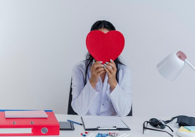 Młoda kobieta lekarz ubrany w medyczną szatę i stetoskop siedzi przy biurku z narzędzi medycznych, trzymając i chowając się za kształt serca na białym tle