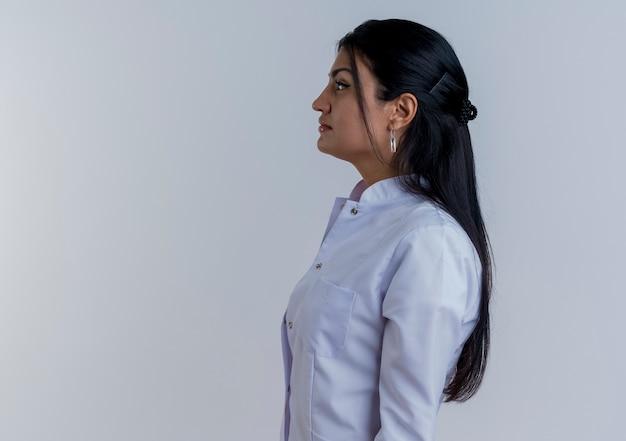 Młoda kobieta lekarz ubrany w medyczną szatę stojącą w widoku profilu patrząc prosto na białym tle