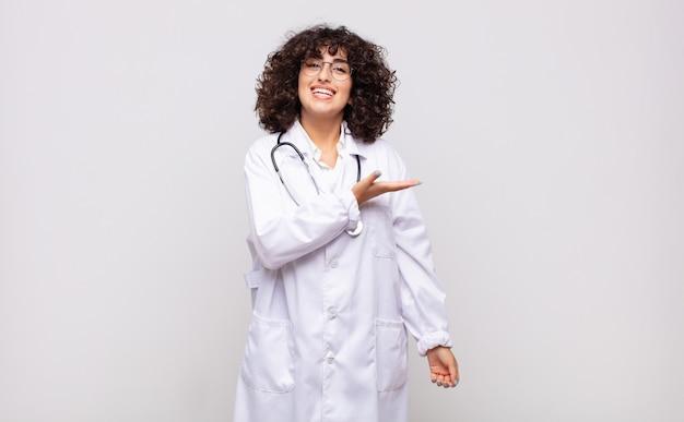 Młoda kobieta lekarz uśmiechając się radośnie, czując się szczęśliwy i przedstawiający koncepcję w przestrzeni kopii z dłoni
