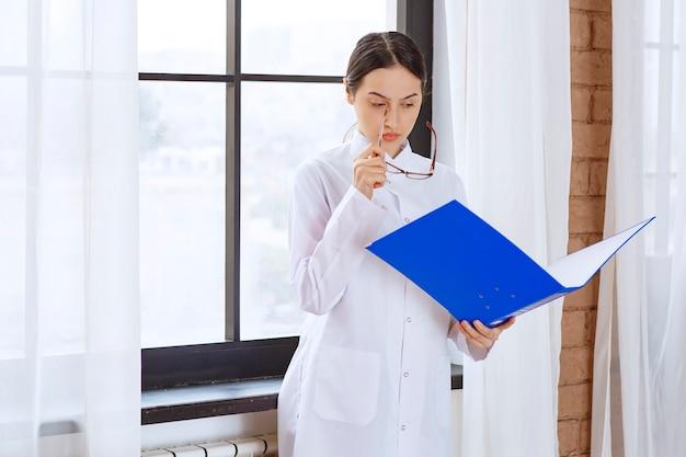 Młoda kobieta lekarz w białym fartuchu, czytając o następnym pacjencie w pobliżu okna.