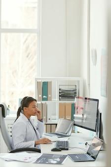 Młoda kobieta lekarz w białym fartuchu siedzi w swoim miejscu pracy i pracuje na komputerze w biurze