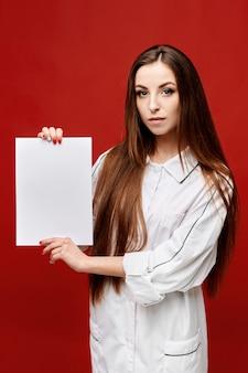 Młoda kobieta lekarz w białym fartuchu z pustą białą kartką papieru w dłoniach. skopiuj miejsce na tekst. pojęcie opieki zdrowotnej i medycyny