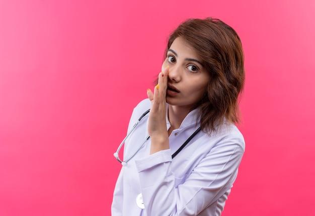 Młoda kobieta lekarz w białym fartuchu ze stetoskopem mówi e sicret z ręką w pobliżu ust stojąc na różowej ścianie