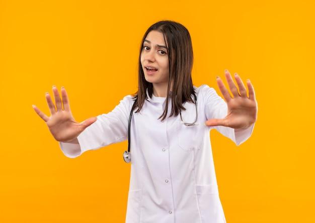 Młoda kobieta lekarz w białym fartuchu ze stetoskopem na szyi każąc przestać śpiewać trzymając się za ręce przestraszona stojąc nad pomarańczową ścianą