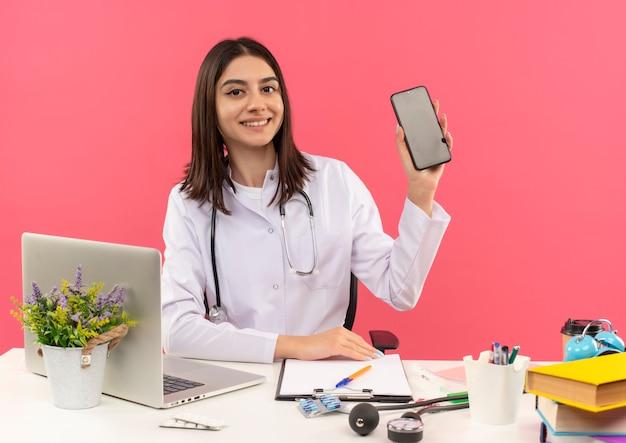 Młoda kobieta lekarz w białym fartuchu ze stetoskopem na szyi pokazuje smartfon uśmiechnięty pewnie siedzący przy stole z laptopem na różowej ścianie