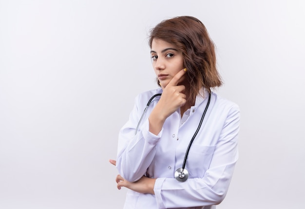 Młoda kobieta lekarz w białym fartuchu ze stetoskopem patrząc na kamery ręką na brodzie z zamyślonym wyrazem twarzy myślenia