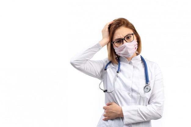 Młoda kobieta lekarz w białym garniturze medycznym ze stetoskopem w białej masce ochronnej pozowanie na biały