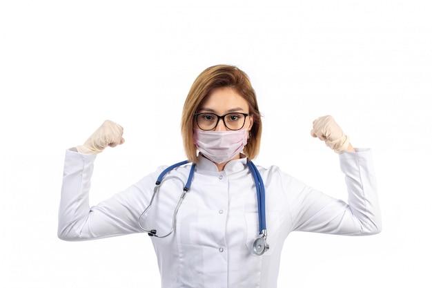 Młoda kobieta lekarz w białym kombinezonie medycznym ze stetoskopem w białej masce ochronnej zginanie na białym