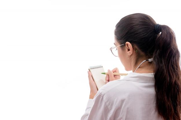 Młoda kobieta lekarz w okularach przepisując w zeszycie
