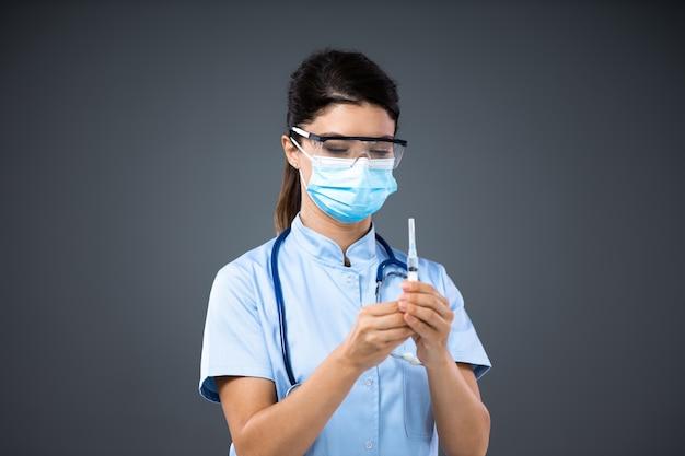 Młoda kobieta lekarz z maską na twarz i okularami ochronnymi na trzymaniu strzykawki i przygotowywaniu się do podania zastrzyku choremu pacjentowi.