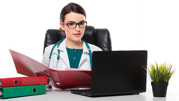 Młoda kobieta lekarz z stetoskop siedzi na biurku w gabinecie lekarskim w białym mundurze na białym tle