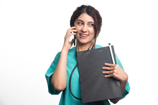 Młoda kobieta lekarz ze schowka i rozmawia przez telefon komórkowy na białym tle