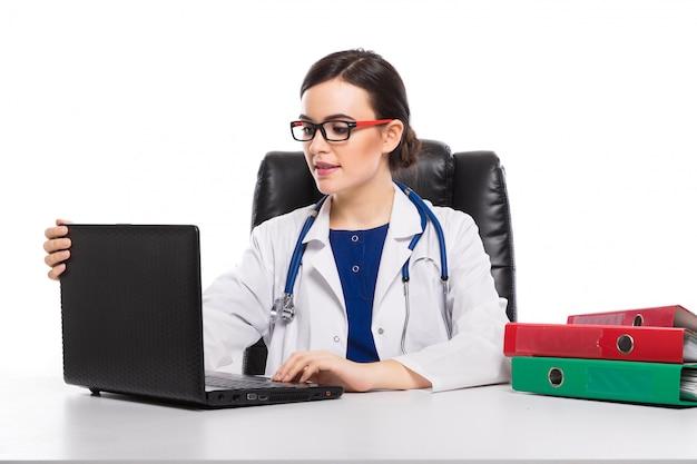 Młoda kobieta lekarz ze stetoskopem siedzi na biurku w gabinecie lekarskim w białym mundurze na białym tle