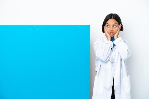 Młoda kobieta lekarza rasy mieszanej z dużym plakatem odizolowała sfrustrowaną i zakrywającą uszy