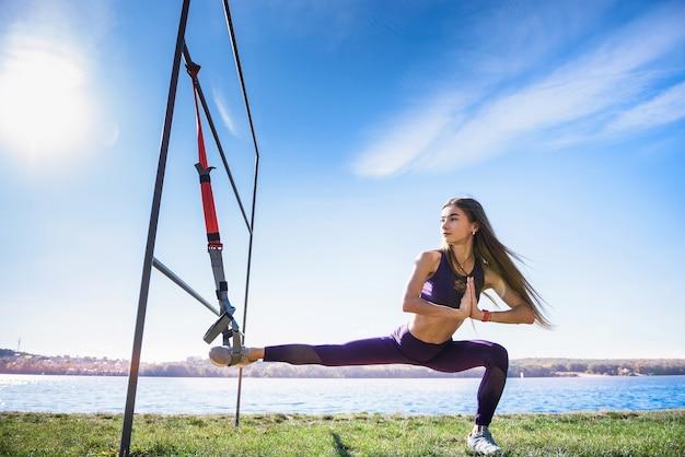 Młoda kobieta lekkoatletka robi poranne ćwiczenia treningowe z trx