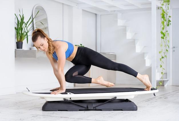Młoda kobieta lekkoatletka robi wysokie deski cross pająk ćwiczenia na surfset