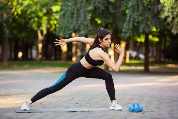 Młoda kobieta lekkoatletka szkolenia na ulicy miasta w letnim słońcu. piękna kobieta ćwiczy, ćwiczy. pojęcie sportu, zdrowego stylu życia, ruchu, aktywności. rozciąganie, brzuszki, abs.