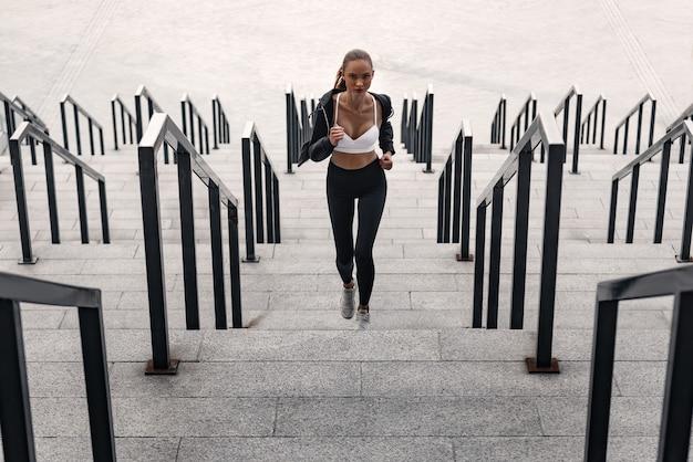 Młoda kobieta lekkoatletycznego bieganie na górze. nosi odzież sportową i białe trampki.