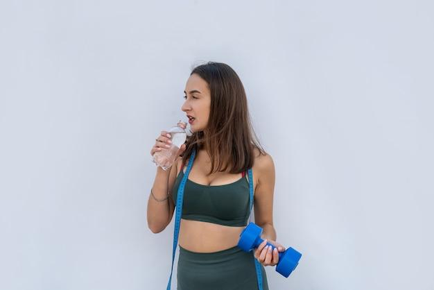 Młoda kobieta lekkoatletycznego gospodarstwa hantle i butelkę wody na białym szarym tle. zdrowy tryb życia