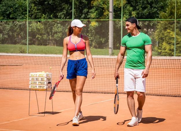 Młoda kobieta lekkoatletycznego, grając w tenisa ze swoim trenerem