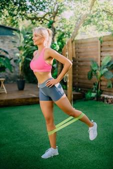 Młoda kobieta lekkoatletycznego robi fitness na trawniku w podwórzu domu, pojęcie zdrowego stylu życia