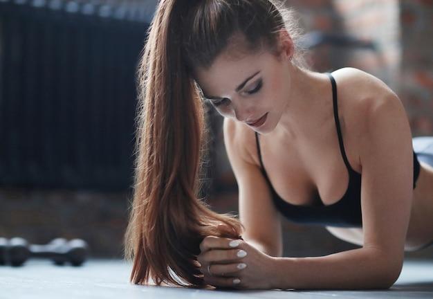 Młoda kobieta lekkoatletycznego robi jej rutynowych ćwiczeń w domu