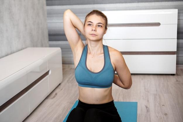 Młoda kobieta lekkoatletycznego robi rozciąganie przed treningiem w domu. trener fitness w domu