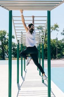 Młoda kobieta lekkoatletycznego robienie ćwiczeń na boisku w lecie