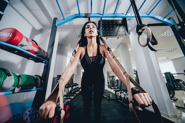 Młoda kobieta lekkoatletycznego szkolenia z trx fitness pasy.