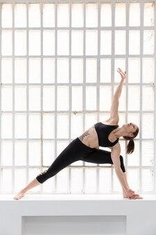 Młoda kobieta lekkoatletycznego w czarnej odzieży sportowej praktykuje jogę obok dużego okna w jej studio. miejsce na tekst.