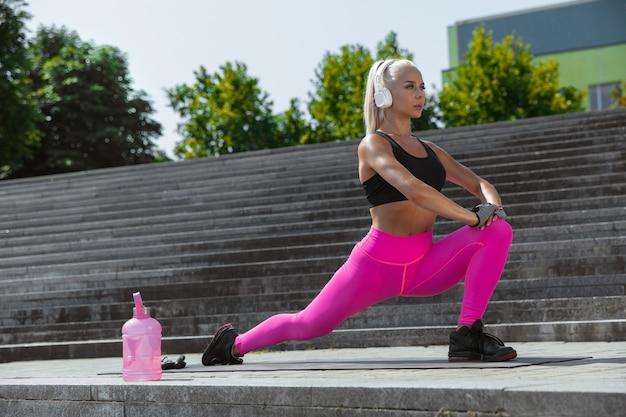 Młoda kobieta lekkoatletycznego w koszuli i białych słuchawkach, pracując, słuchając muzyki na ulicy na świeżym powietrzu. wykroki i rozciąganie. pojęcie zdrowego stylu życia, sportu, aktywności, utraty wagi.