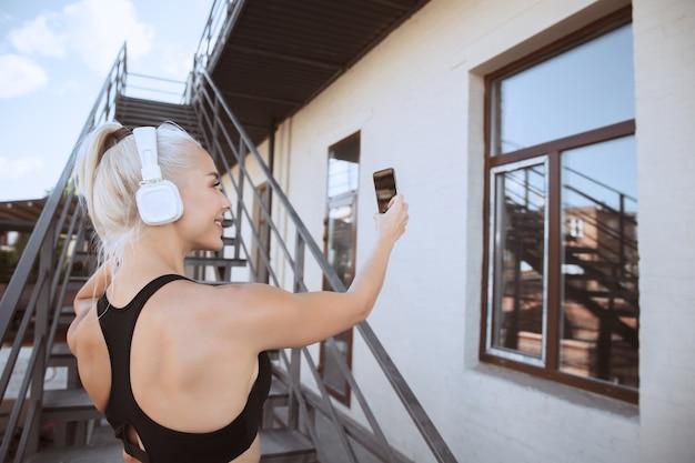 Młoda kobieta lekkoatletycznego w koszuli i białych słuchawkach, pracująca, słuchanie muzyki na schodach na zewnątrz. robienie selfie. pojęcie zdrowego stylu życia, sportu, aktywności, utraty wagi.