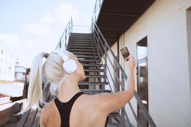 Młoda kobieta lekkoatletycznego w koszuli i białych słuchawkach, pracująca, słuchanie muzyki na schodach na zewnątrz