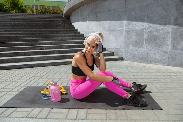 Młoda kobieta lekkoatletycznego w koszuli i białych słuchawkach, pracująca, słuchanie muzyki na ulicy na świeżym powietrzu