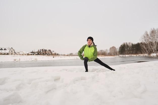 Młoda kobieta lekkoatletycznego w kurtce wykonuje wypad na bok na śniegu podczas treningu na brzegu zimą