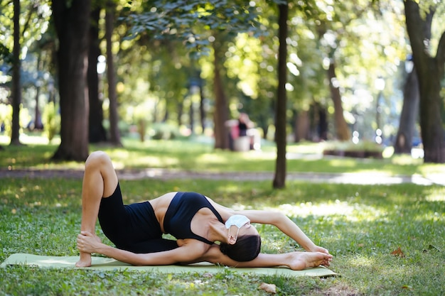 Młoda kobieta lekkoatletycznego w medycznej masce ochronnej, joga w parku rano, szkolenie kobiet na macie do jogi