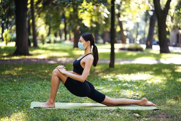 Młoda kobieta lekkoatletycznego w medycznej masce ochronnej, joga w parku rano, trening kobiet na macie do jogi