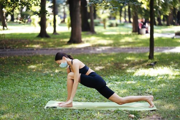 Młoda kobieta lekkoatletycznego w medycznej masce ochronnej, robi joga w parku rano