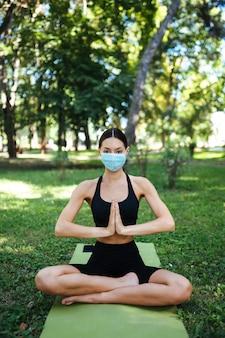 Młoda kobieta lekkoatletycznego w medycznej masce ochronnej, robi joga w parku w godzinach porannych