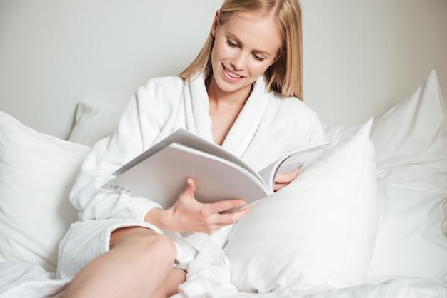Młoda kobieta, leżąc na łóżku w pokoju hotelowym