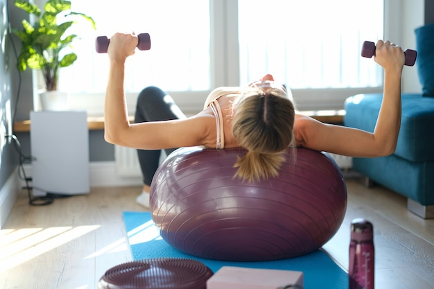 Młoda kobieta leżąc na piłce podnosi hantle. koncepcja ćwiczeń równowagi i wytrzymałości