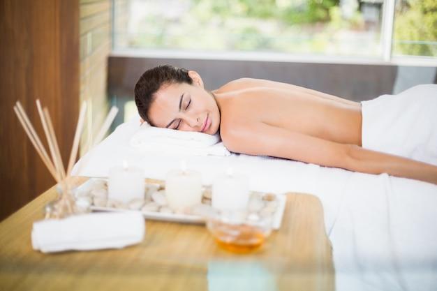 Młoda kobieta, leżąc na stole do masażu