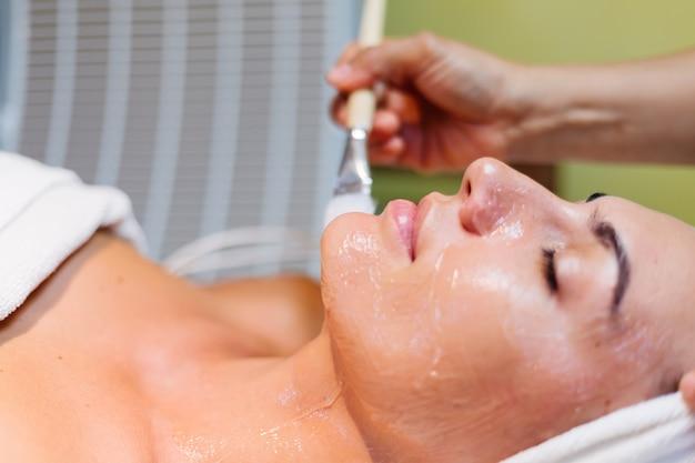 Młoda kobieta, leżąc na stole kosmetyczki podczas zabiegu odmładzania