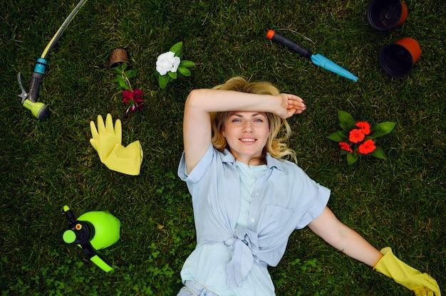 Młoda kobieta, leżąc na trawie w ogrodzie wśród narzędzi ogrodniczych, widok z góry. kobieta ogrodniczka zajmuje się roślinami outdoorowymi, ogrodnictwem hobbystycznym, florystycznym stylem życia i wypoczynkiem