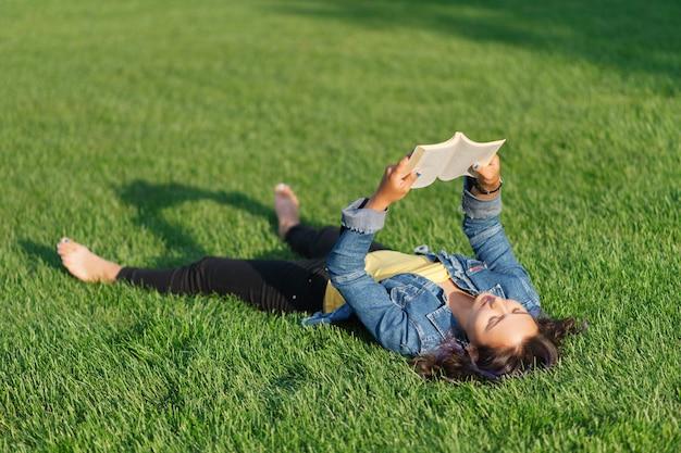 Młoda kobieta, leżąc na zielonym trawniku w parku w lecie i czytając książkę