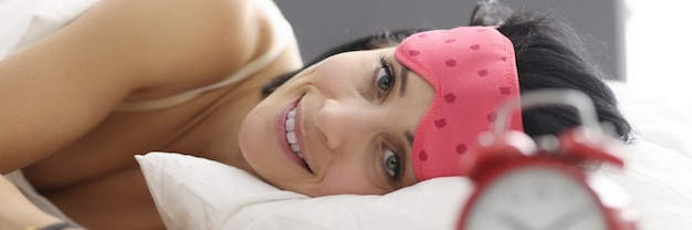 Młoda kobieta leżąc w łóżku noszenie maski snu. koncepcja porannego nastroju