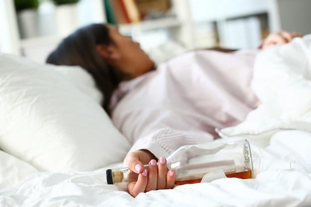 Młoda kobieta, leżąc w łóżku śmiertelnie pijany