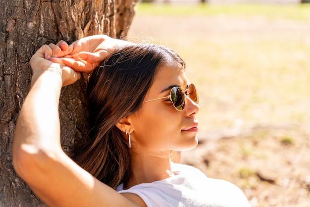 Młoda kobieta leżąca obok drzewa i ciesząca się słońcem