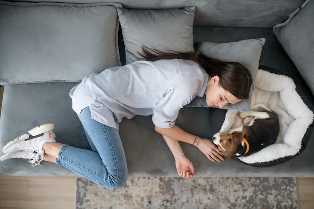 Młoda kobieta leżąca obok szczeniaka i ucinająca sobie drzemkę