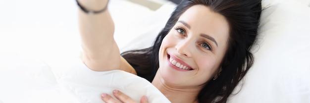 Młoda kobieta leżąca w łóżku i biorąca koncepcję mediów społecznościowych selfie
